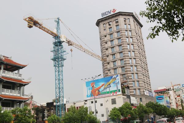 Cần cẩu đập vào tòa cao ốc ở Sài Gòn, đá rơi đè nát đầu xe sang - 1