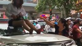 Nữ tài xế taxi mặc váy ngồi nóc ô tô chống đối CSGT
