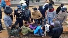 Nhóm thanh niên bịt mặt khiêng dân ra khỏi công trường để thi công