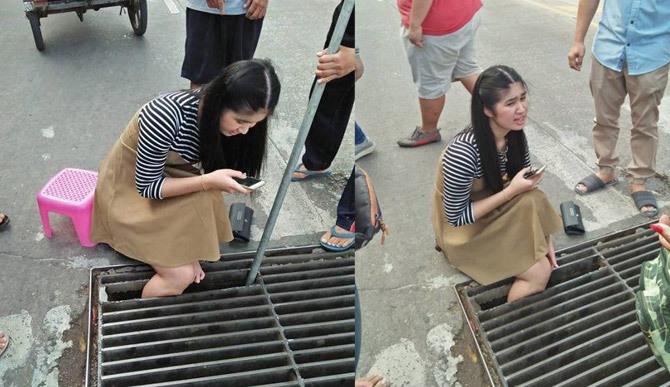 Mải xem điện thoại, cô gái tụt chân xuống miệng cống ngầm