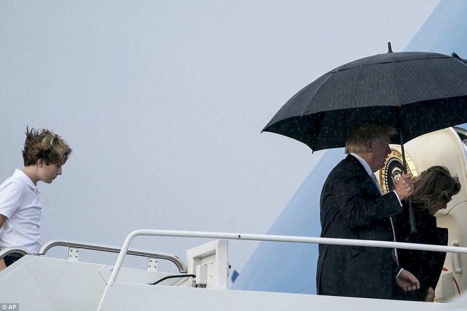 Ông Trump cầm ô đi trước vợ con giữa trời mưa