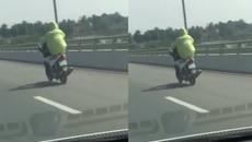 Nam thanh niên đi xe máy bằng chân trên cầu vượt biển