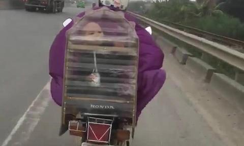 Mẹ đi xe máy chở con trong lồng chim để tránh rét?