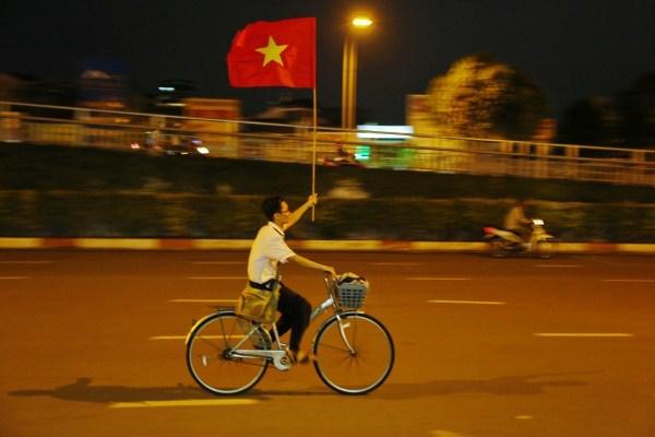 Nam sinh Sài Gòn thong dong đạp xe với lá cờ đỏ được người qua đường tặng